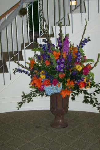 A large urn full of summer flowers greeted the wedding guests as they came