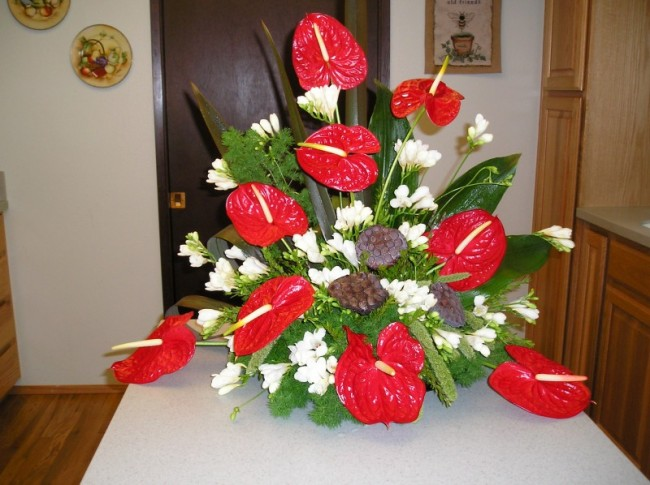Anthuriums and freesia accented with lotus pods for buffet centerpiece