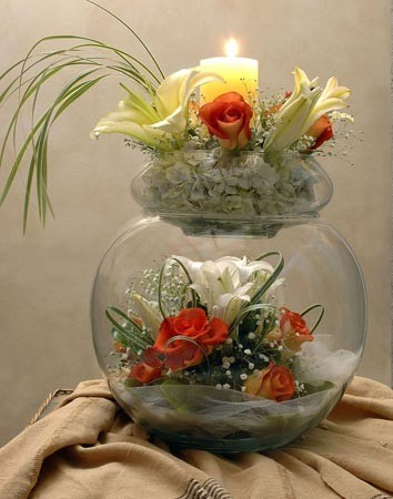 This wedding centerpiece features an open spherical glass vase with a