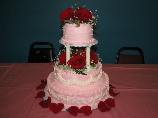 This pink wedding cake is amazing It is tediously decorated with tiny white