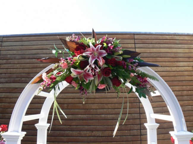 Lilies and red roses make this wedding archway picture perfect