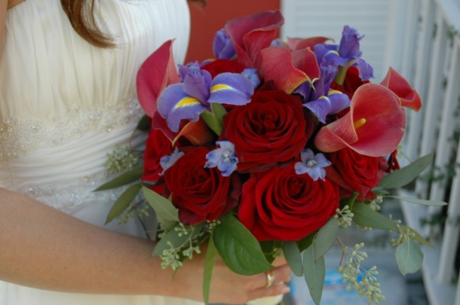 This red and purple bridal bouquet is created with red calla lilies blue