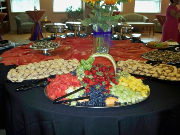 This wedding reception food table is elaborately set with delicious foods