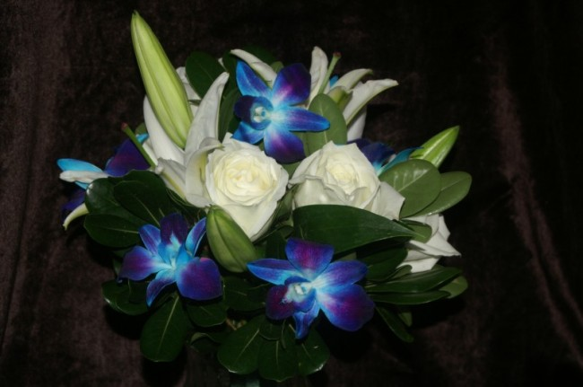 This stunning wedding bouquet is filled with blue orchids white lilies and