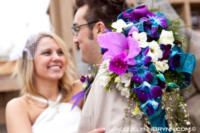 A happy bride holding a radiant blue purple orchid bridal bouquet