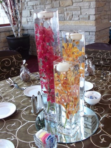 This floral centerpiece shows three vases with red and gold orchids
