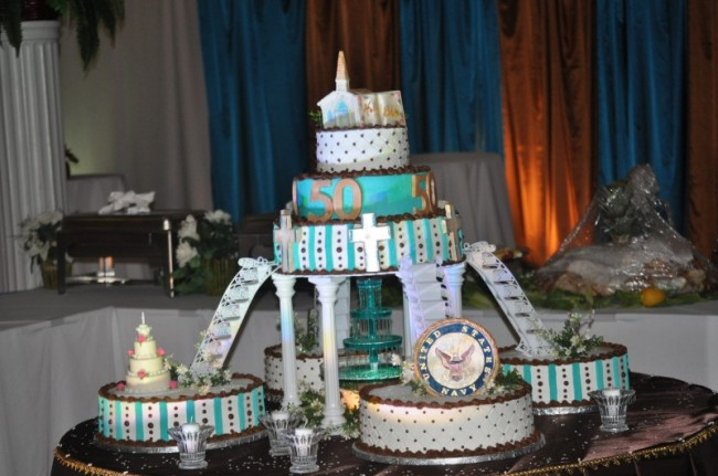 Four cakes in brown teal black and white surround a larger three tier