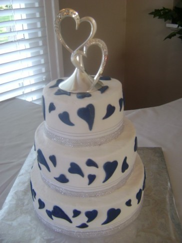 This three tier white wedding cake is all about love With navy blue fondont