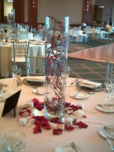 Surrounding the vase are white candles and red rose petals