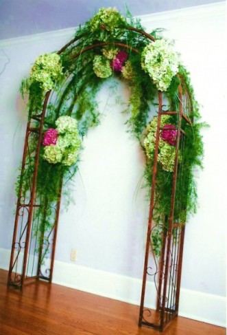 This beautiful wedding arch features green and pink wedding flowers