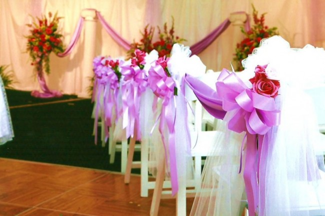 This wedding ceremony is adorned with beautiful white tulle pink ribbon and