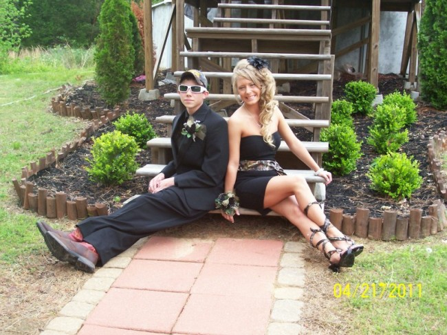 She wears an amazing black prom dress with a camo sash and matching shoes