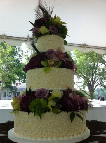 A gorgeous 3 tiered wedding cake with swirl design is accented with roses