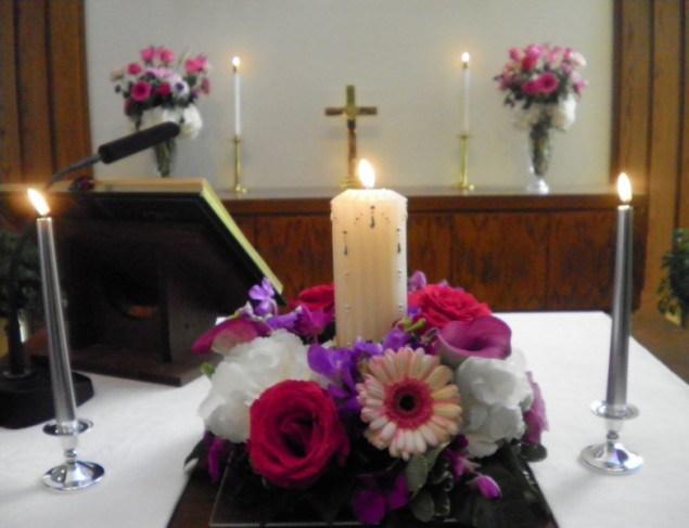 This unity candle is surrounded by gorgeous wedding flowers