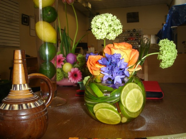 It features colorful flowers and is accented with limes wedding centerpieces