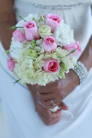 This gorgeous bride is holding a pink cream wedding bouquet filled with