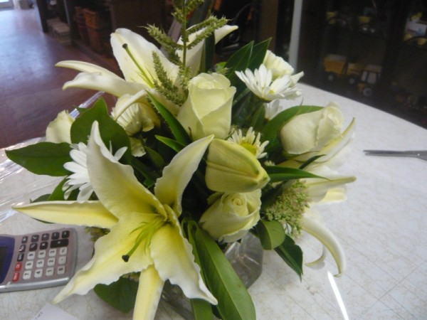A gorgeous reception centerpiece with White Lilies arranged in a glass cube