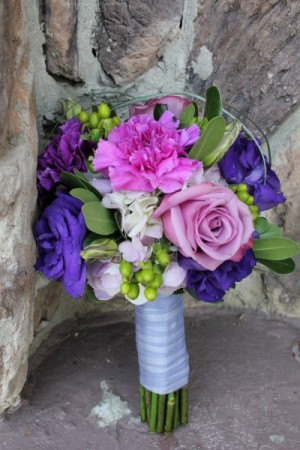 A gorgeous wedding bouquet that features pink and purple flowers