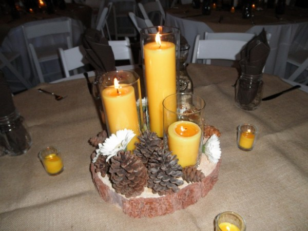 This reception centerpiece features beautiful candles pine cones and white
