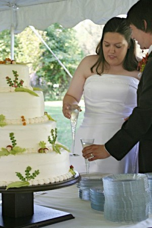 Bride and grown cut the fall wedding cake for presentation at an outdoor